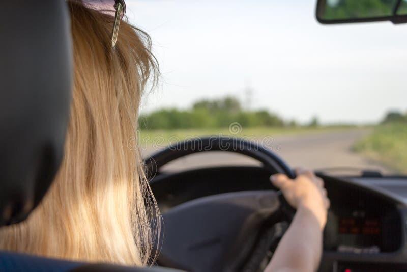 特写镜头视图从后面驾驶在乡下公路的年轻女人一辆汽车 平安的旅行概念 库存照片