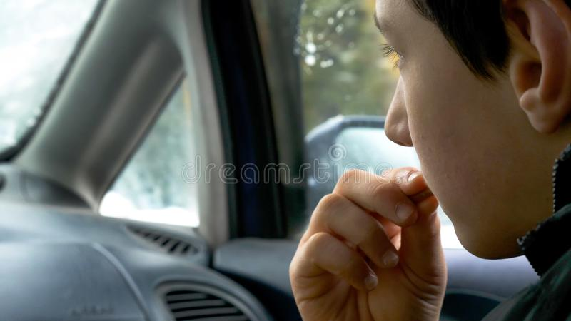 特写镜头视图儿童拿着和吃饼干的男孩手,当旅行在汽车时 库存图片