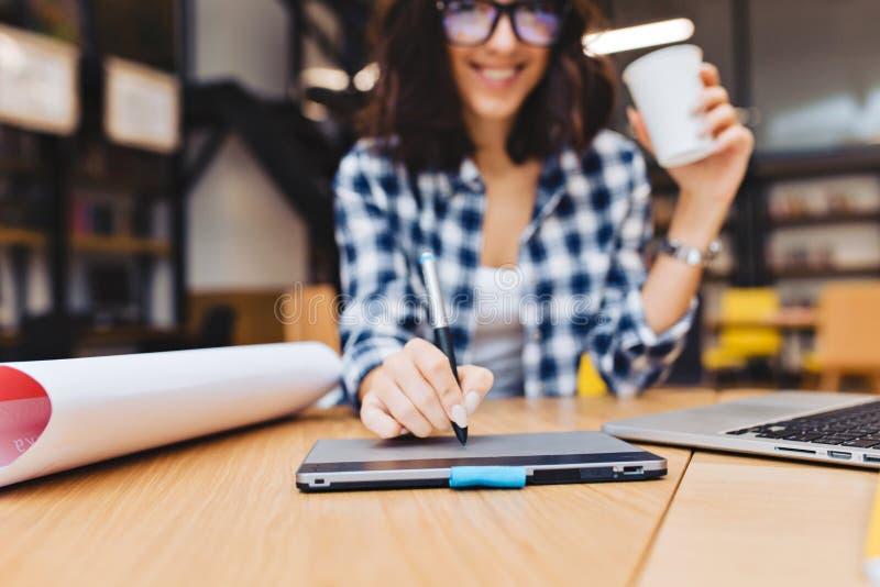 特写镜头设计在图书馆周围工作材料的桌上的年轻深色的妇女的图象手 膝上型计算机,创造性的工作 图库摄影