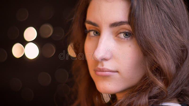 特写镜头转动和看照相机的年轻有吸引力的白种人女性面孔侧视图射击与在的bokeh光 图库摄影