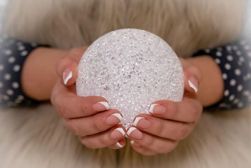 特写镜头选择聚焦摄影 有一闪烁的圣诞装饰的妇女的手 圣诞节球 免版税库存图片