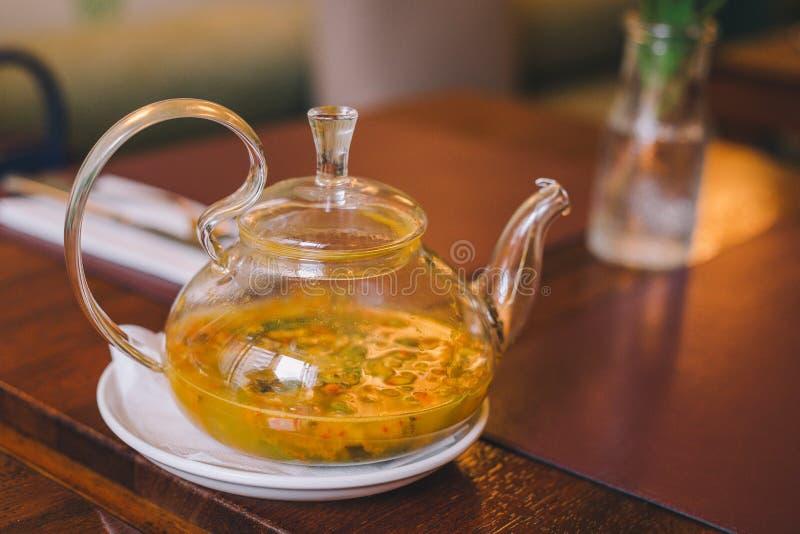 特写镜头透明玻璃茶壶用海在桌上的鼠李茶 库存图片