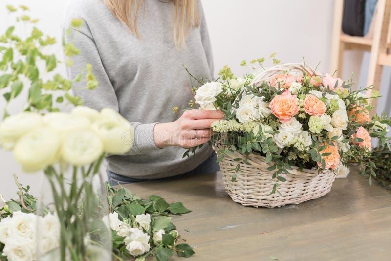 特写镜头递女性卖花人花卉车间-做美好的花构成在柳条的妇女花束 库存照片