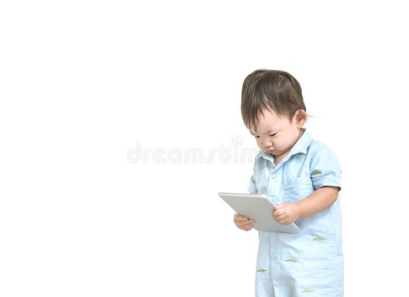 特写镜头逗人喜爱的亚洲孩子看看片剂在他的手上有在工作概念的白色背景隔绝的严肃的面孔的与拷贝温泉 免版税库存图片