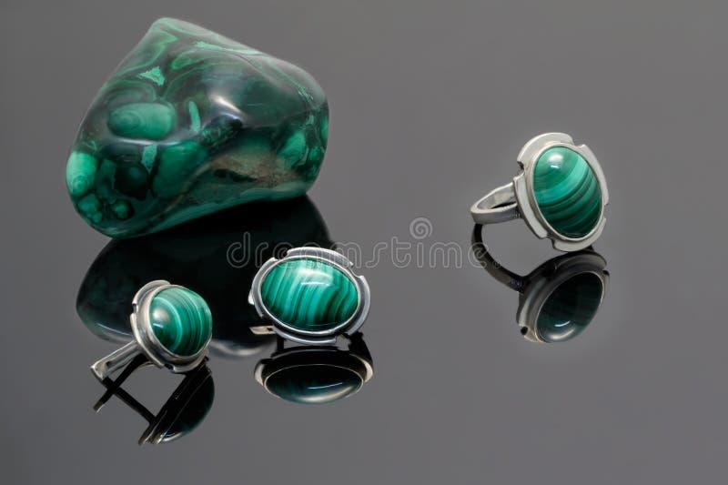 特写镜头银色耳环和圆环与绿沸铜在绿沸铜背景向片断扔石头在黑丙烯酸酯的书桌上 库存图片