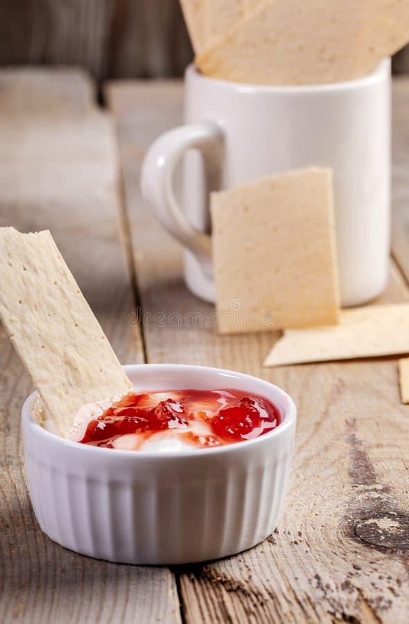 特写镜头陶瓷碗用酸性稀奶油和草莓酱用在老木桌上的麦子薄脆饼干 免版税库存照片