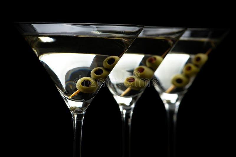 特写镜头马蒂尼鸡尾酒喝用忠心于在黑色的橄榄 免版税库存图片