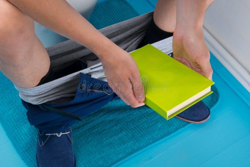 特写镜头,一个人在卫生间里,坐洗手间,与下来他的裤子和拿着书 免版税库存图片