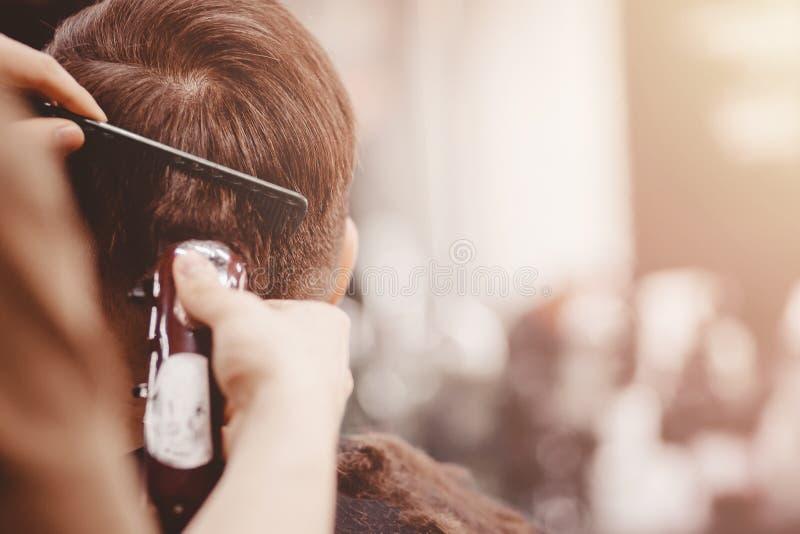 特写镜头,主要美发师做与剪刀梳子的发型 概念理发店 免版税库存图片