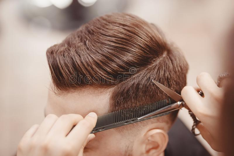 特写镜头,主要美发师做与剪刀梳子的发型 概念理发店 免版税库存照片