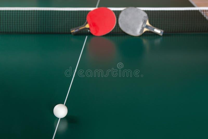 两副乒乓球球拍和一个球在一个选材台上 皇族释放例证