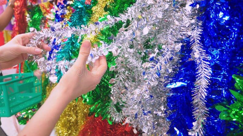 特写镜头,买圣诞装饰的女性手 女孩选择圣诞节闪亮金属片 新的准备的年 免版税库存照片