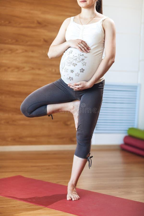 特写镜头,健康概念 年轻美丽的孕妇在一条腿在体育中心做瑜伽锻炼,站立 免版税库存图片