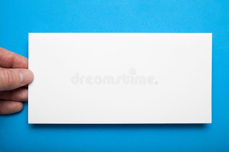 特写镜头,布局DL飞行物在手中在蓝色背景 免版税库存照片