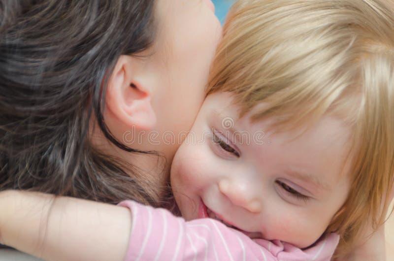 特写镜头,拥抱与妈妈的女婴 免版税库存照片