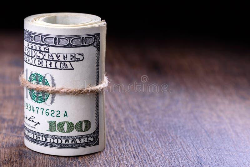 特写镜头,滚动的美国美元钞票宏指令在左边的 木背景 免版税库存照片