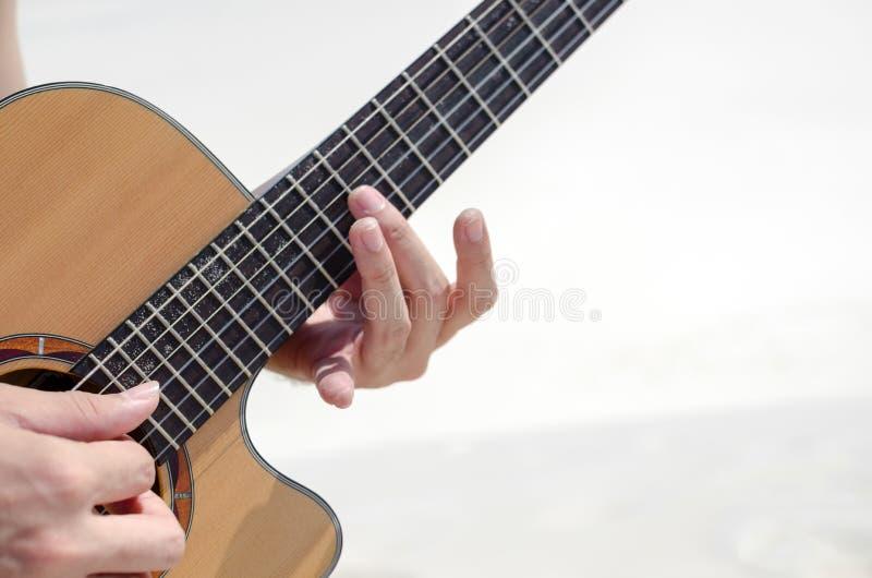 特写镜头:弹吉他的人他的手指 图库摄影