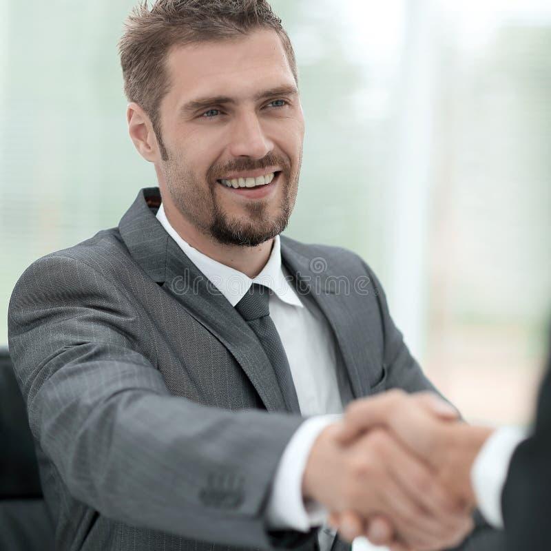 特写镜头 商务伙伴握手在书桌上的 免版税库存图片