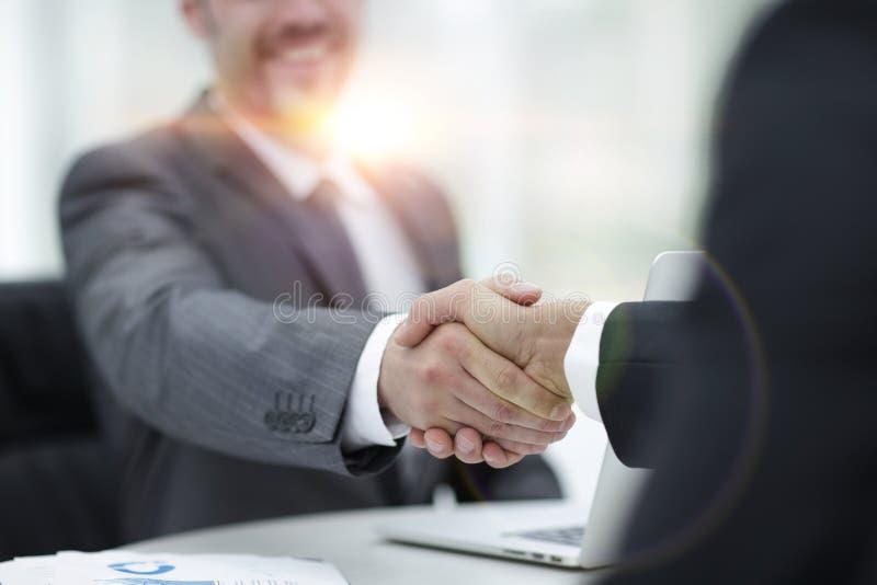特写镜头 商务伙伴握手在书桌上的 库存图片