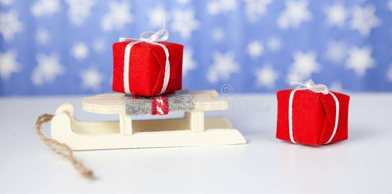 特写镜头 在圣诞老人项目雪橇的圣诞礼物箱子,在蓝色背景 免版税图库摄影