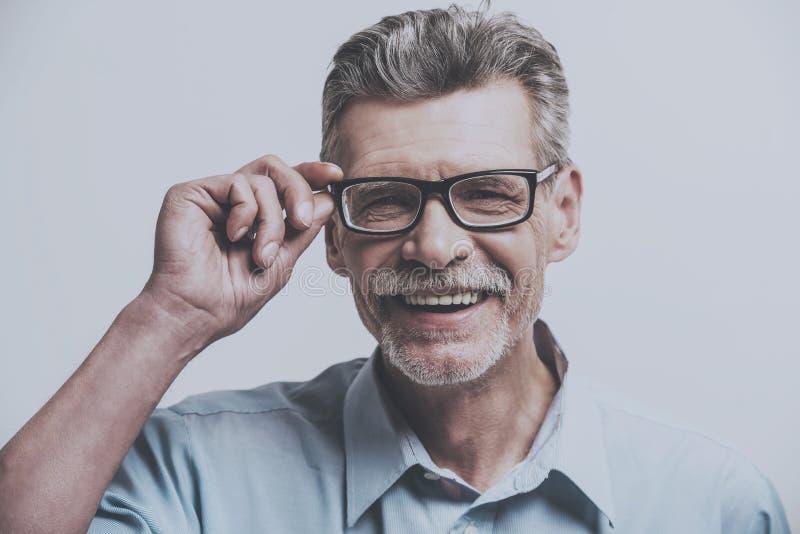 特写镜头 在玻璃的微笑的资深男性在灰色背景 免版税库存图片