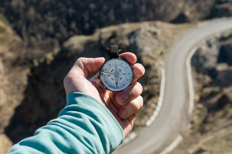 特写镜头A人` s手拿着口袋指南针反对山路和森林的背景概念的室外 免版税库存图片
