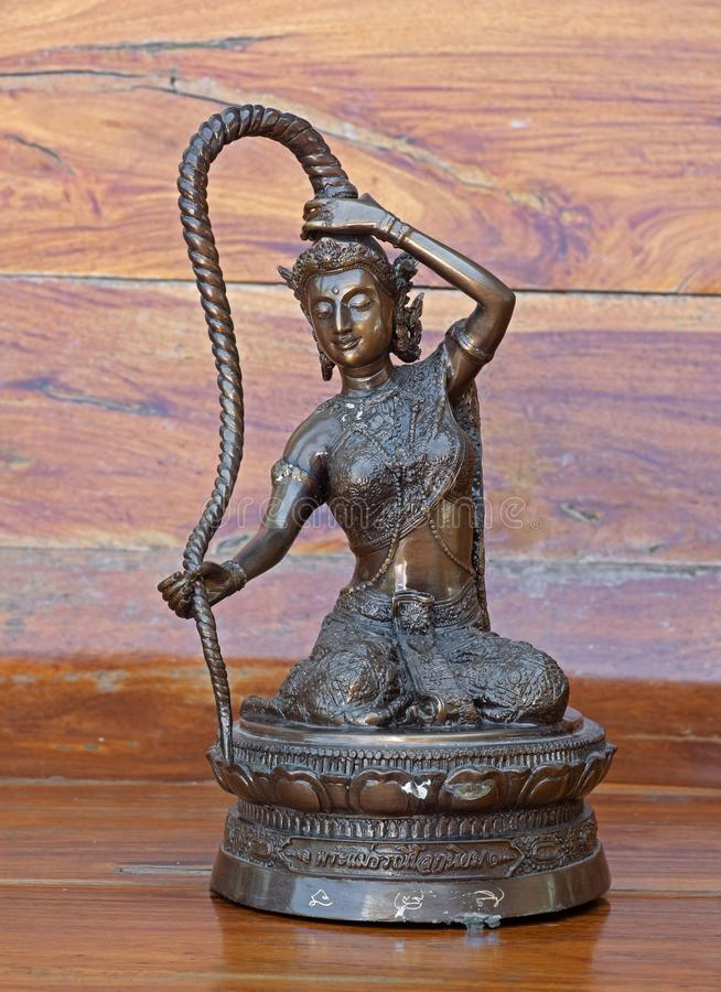 特写镜头Phra Mae Thorani女神雕象在木背景隔绝了 免版税库存图片