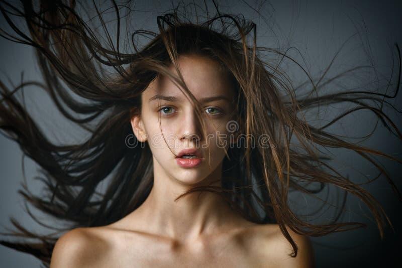 特写镜头一个性感的深色的女孩的秀丽画象有飞行头发的 免版税库存图片