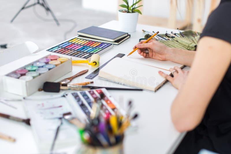 特写镜头一份女性画家图画草稿的角度图在写生簿的使用铅笔 速写在艺术演播室的艺术家与 免版税库存照片