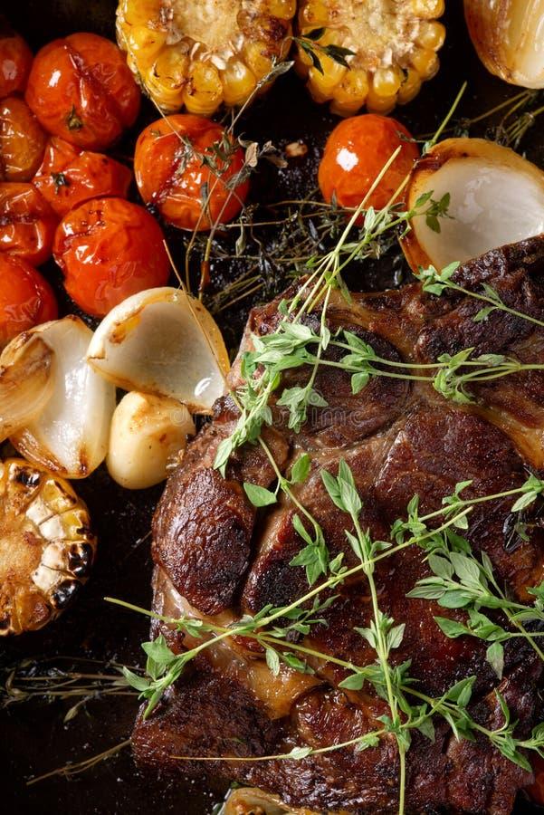特写镜头与菜的牛排在煎锅 免版税库存图片