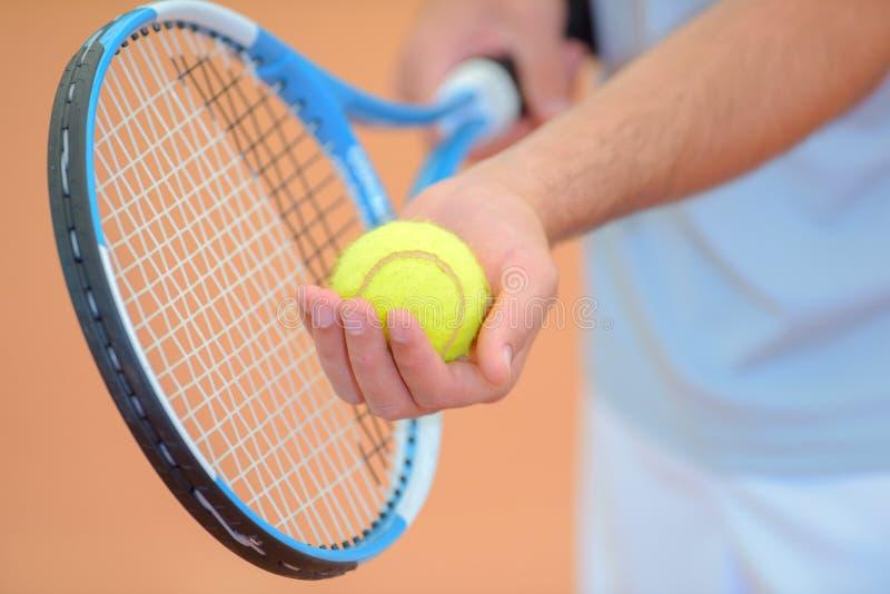 特写镜头人保持平衡服务在网球 免版税库存图片