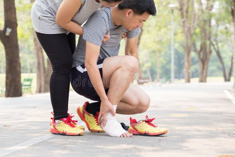 特写镜头伤害行程肌肉痛赛跑者连续体育运动弄脏大腿涉及 人在扭转的被扭伤的脚腕和得到帮助下 免版税库存照片