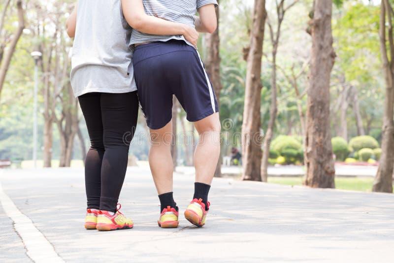 特写镜头伤害行程肌肉痛赛跑者连续体育运动弄脏大腿涉及 人在扭转的被扭伤的脚腕和得到帮助下 库存图片