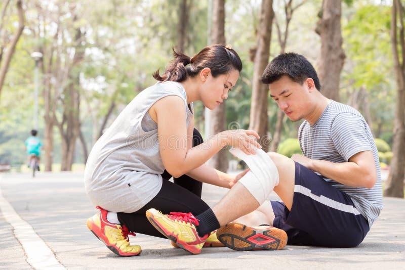 特写镜头伤害行程肌肉痛赛跑者连续体育运动弄脏大腿涉及 人在扭转的被扭伤的膝盖和得到帮助f下 图库摄影