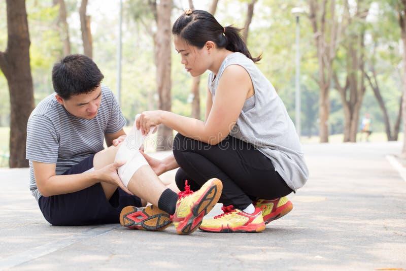 特写镜头伤害行程肌肉痛赛跑者连续体育运动弄脏大腿涉及 人在扭转的被扭伤的膝盖和得到帮助f下 库存照片