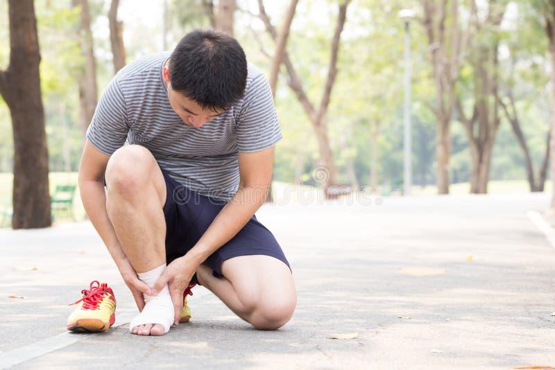 特写镜头伤害行程肌肉痛赛跑者连续体育运动弄脏大腿涉及 充满痛苦的人在脚腕,当跑步时 免版税图库摄影