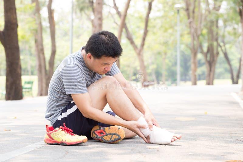 特写镜头伤害行程肌肉痛赛跑者连续体育运动弄脏大腿涉及 充满痛苦的人在脚腕,当跑步时 免版税库存图片
