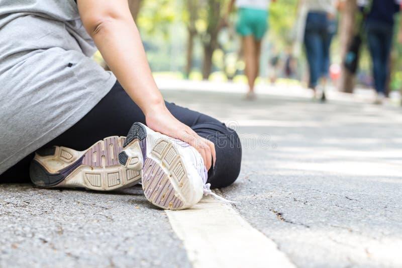 特写镜头伤害行程肌肉痛赛跑者连续体育运动弄脏大腿涉及 充满痛苦的妇女在脚腕,当跑步时 库存图片