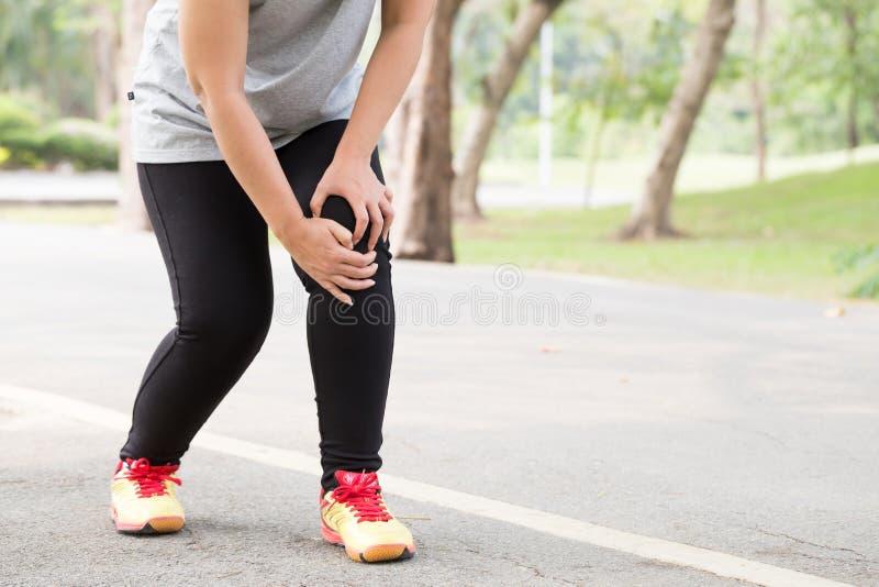 特写镜头伤害行程肌肉痛赛跑者连续体育运动弄脏大腿涉及 充满痛苦的妇女在膝盖,当跑步时 库存照片