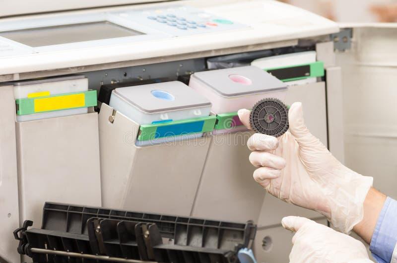 特写镜头修理打破的复印机的射击技术员 免版税图库摄影