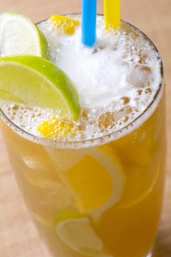 特写镜头冰茶用奶油,冰,黄色和绿色柠檬 库存图片
