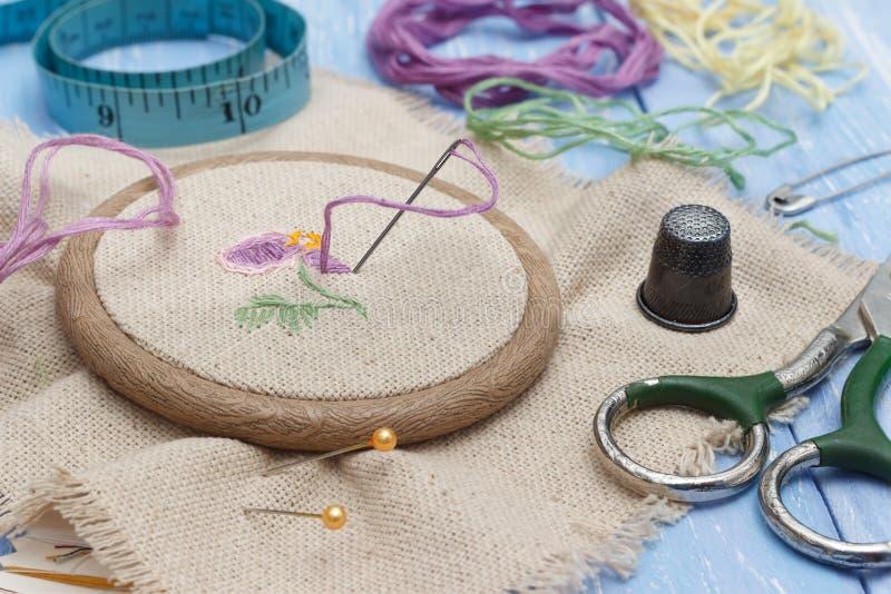特写镜头在木绣花绷的螺纹和亚麻布织品的针线、剪刀、顶针和缝合的米在蓝色木 库存图片