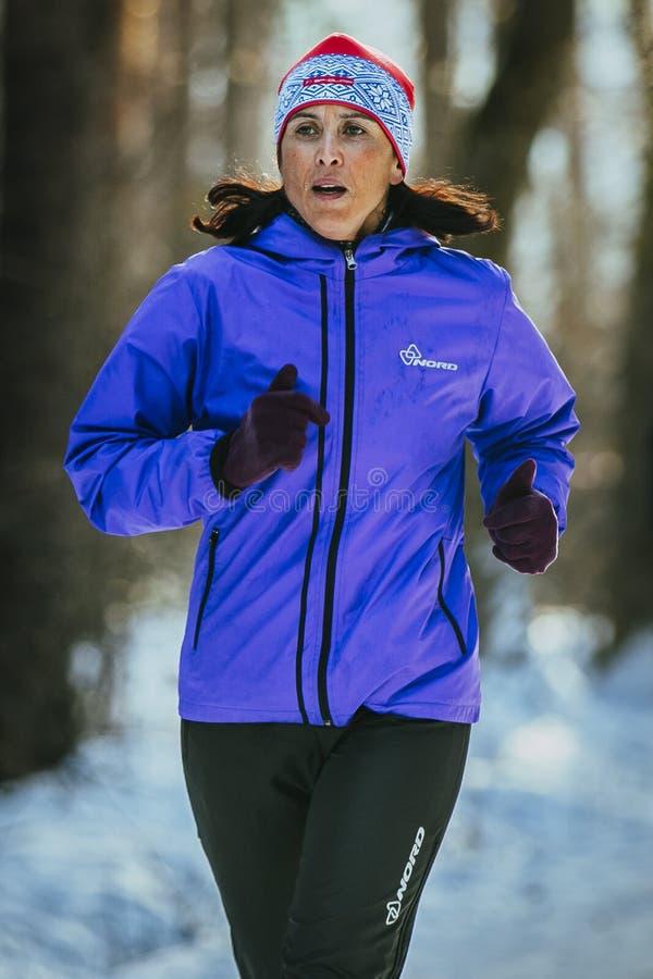 特写镜头女子运动员中年赛跑通过多雪的公园 库存照片