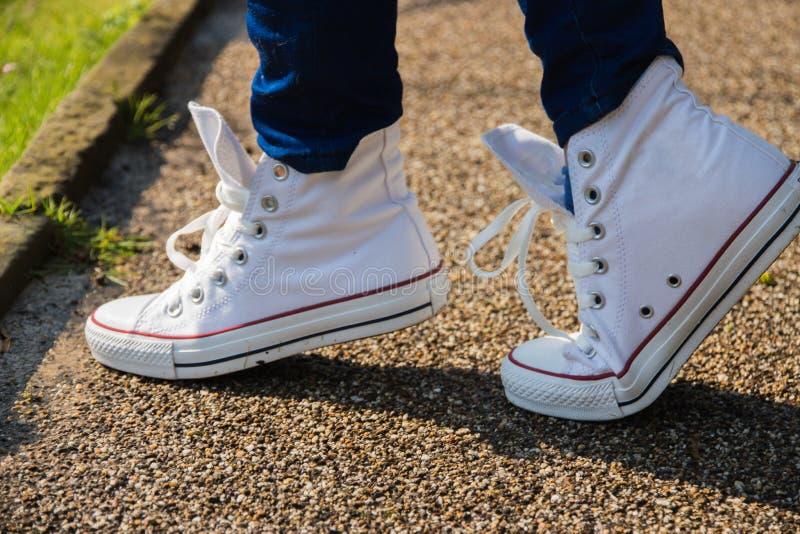 特写镜头女孩在白色运动鞋的` s腿在沥青背景 库存图片