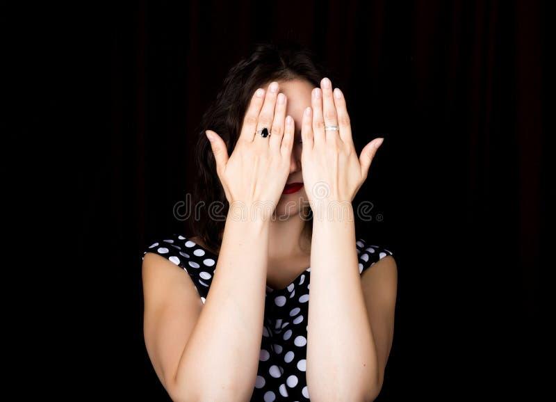 特写镜头妇女看直接入在黑背景的照相机 盖她的眼睛的笑的妇女用她的手 免版税库存照片