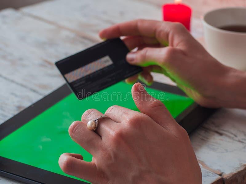 特写镜头妇女` s递拿着信用卡和使用空的屏幕片剂个人计算机网上购物的 免版税库存图片
