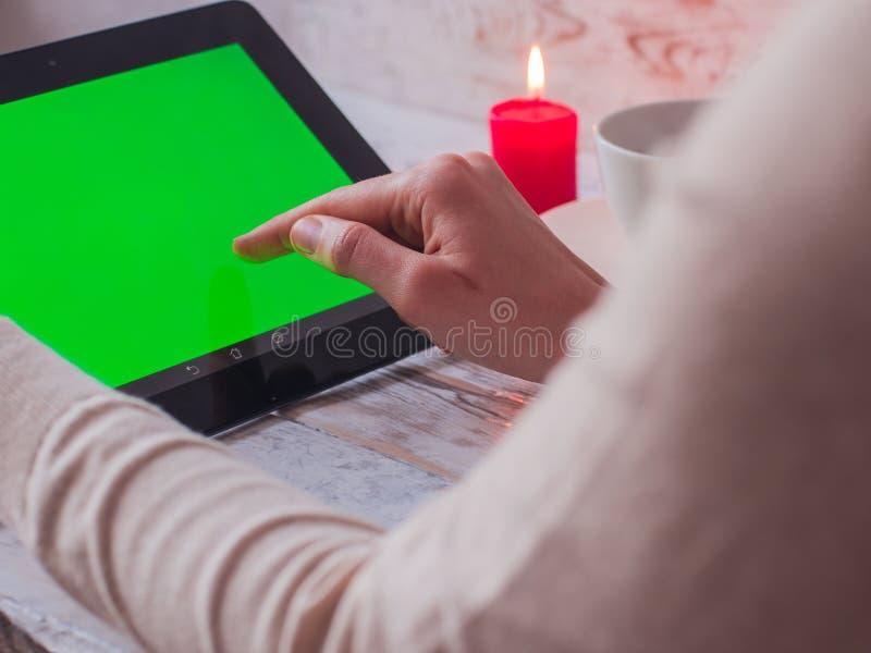 特写镜头妇女` s递拿着在咖啡馆的一台绿色屏幕片剂个人计算机 图库摄影