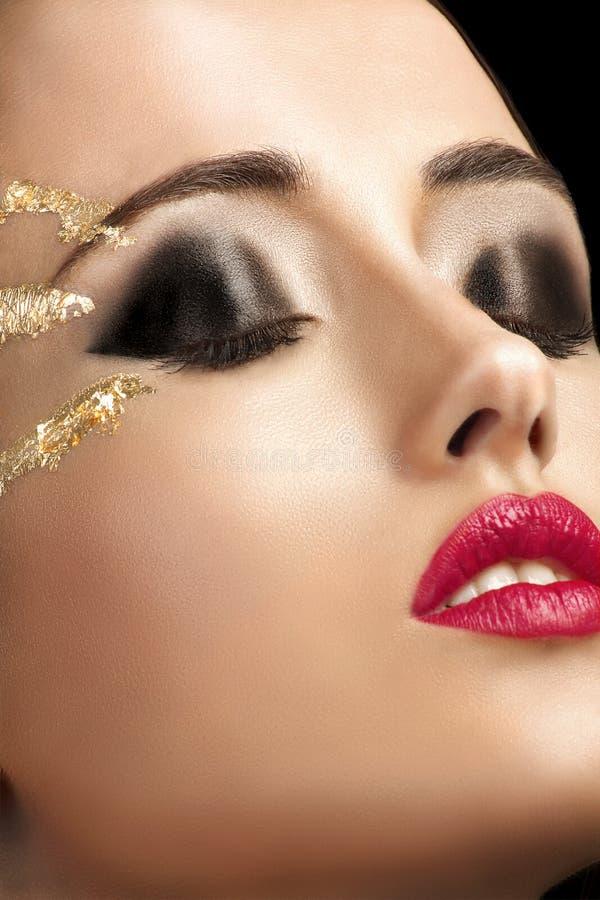 特写镜头射击了与金黄光亮的眼睛构成的女性面孔 库存图片