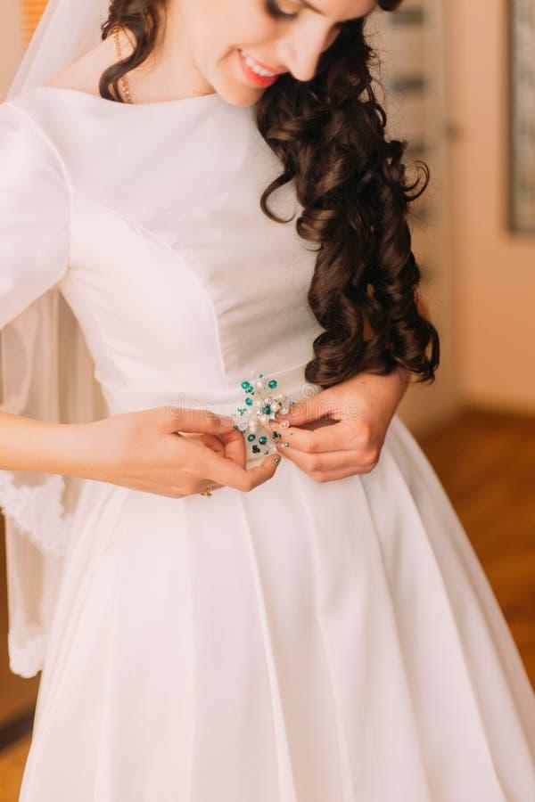 特写镜头射击了固定她的选矿的葡萄酒白色礼服的典雅,深色的新娘在婚姻前 免版税库存图片