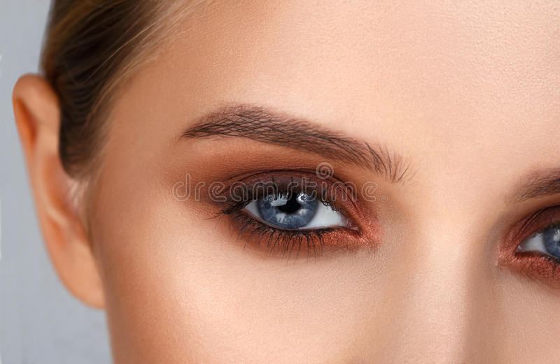 特写镜头射击了在发烟性眼睛样式的女性眼睛构成 免版税库存图片